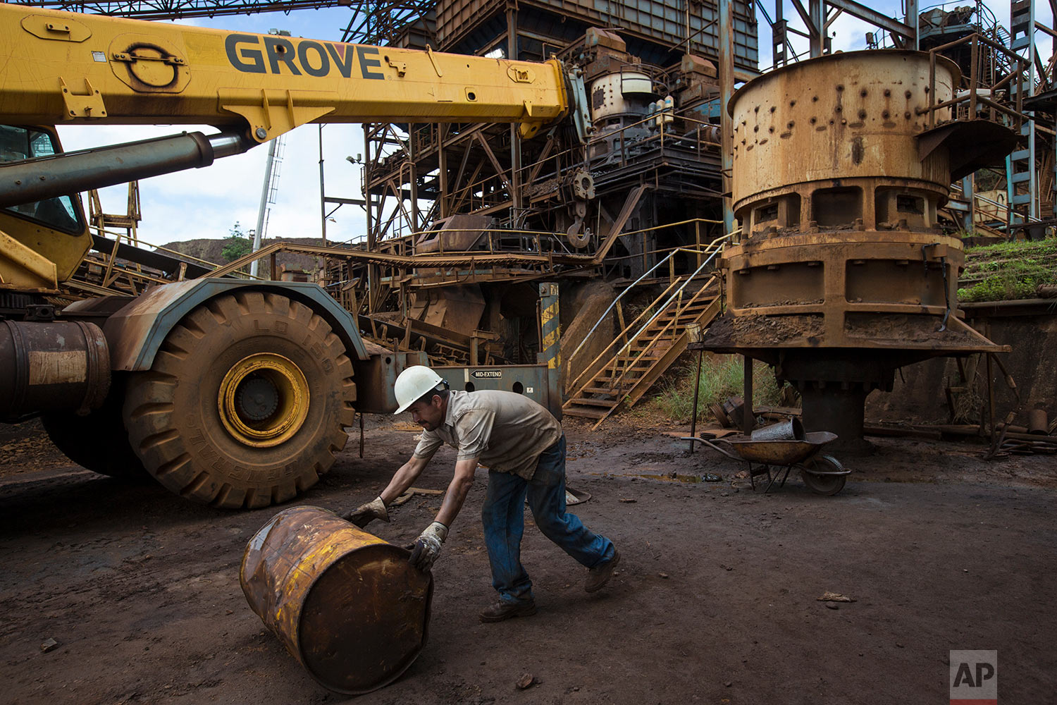 In this Nov. 2, 2017 photo, a Ferrominera Orinoco worker rolls a an empty barrel in Ciudad Piar, Bolivar state, Venezuela. Venezuela sits atop the world's largest oil reserves, but low crude prices and a plunge in production has left it in an economic free fall. (AP Photo/Rodrigo Abd)