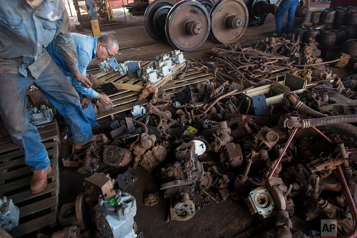 In this Nov. 1, 2017 photo, workers look for spares form a pile of parts cannibalized from other locomotives at Ferrominera Orinoco, in Ciudad Guayana, Bolivar state, Venezuela. Finding spare parts stripped from one broken-down locomotive to repair another in a desperate attempt to keep a once-thriving iron ore mining company running. (AP Photo/Rodrigo Abd)