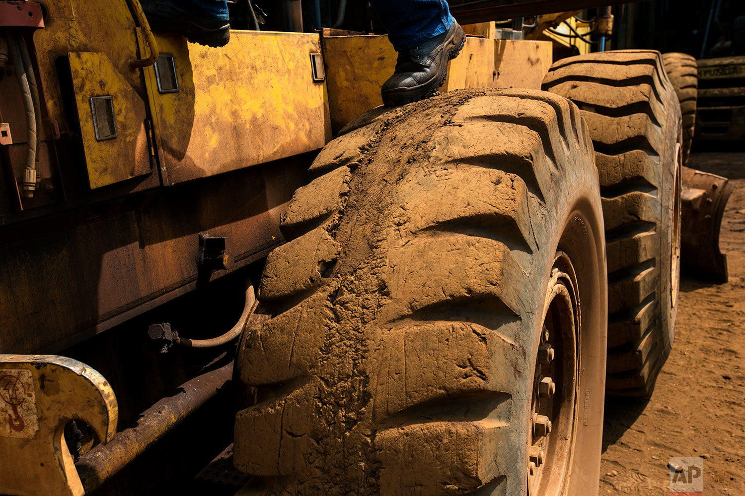 In this Nov. 4, 2017 photo, a worker repairs a truck at workshop at Ferrominera Orinoco, in Ciudad Piar, Bolivar state, Venezuela. The massive truc runs on a tire so badly worn that strips of rubber tread are missing. (AP Photo/Rodrigo Abd)