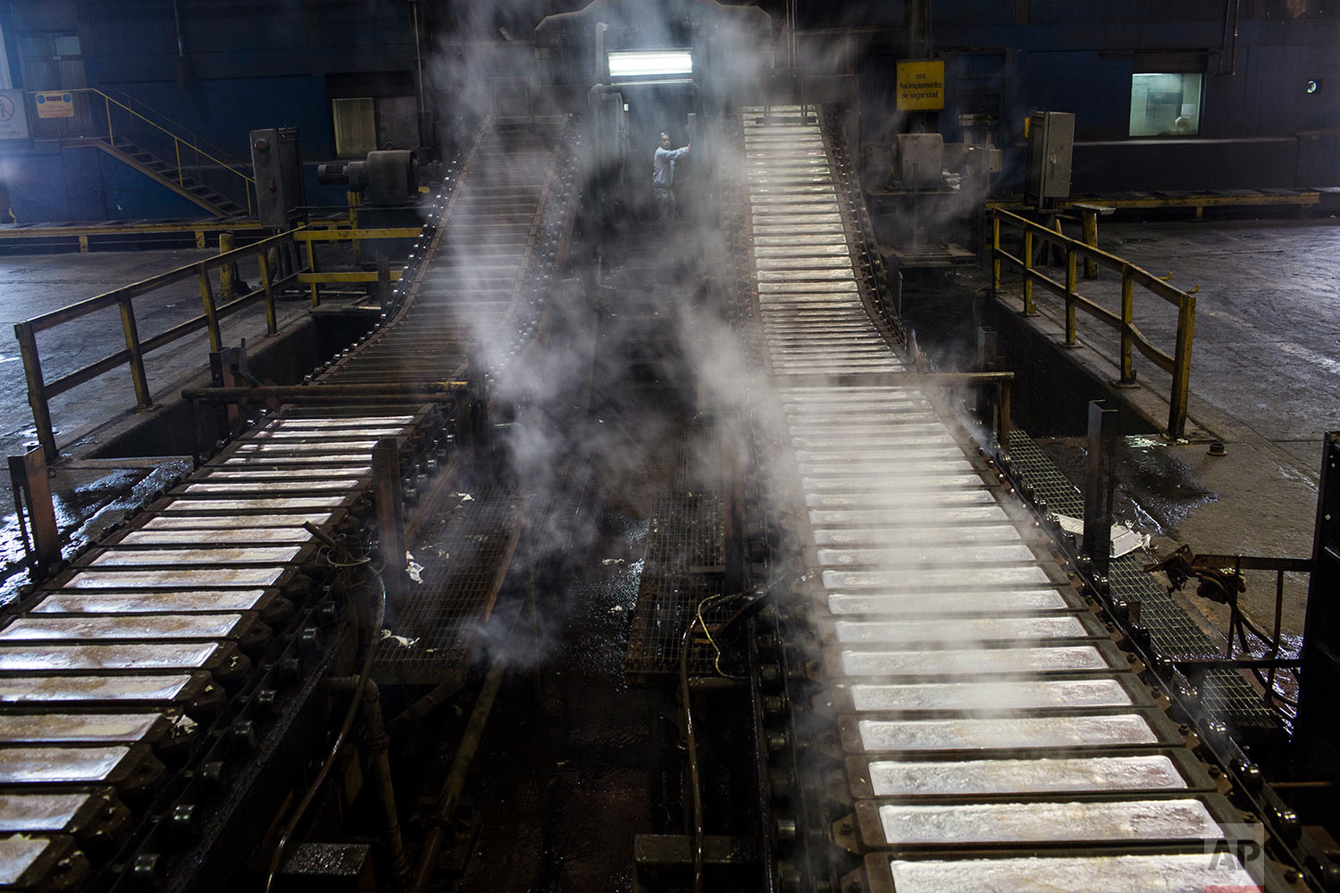 In this Nov. 6, 2017 photo, a worker supervises the filling of aluminium bars in Venalum, in Ciudad Guayana, Bolivar state, Venezuela. U.S. companies in the 1950s zeroed in on Venezuela's vast resources, pouring money into factories for turning iron ore to steel and bauxite for aluminum as well as rails and river ports for shipping it to market. (AP Photo/Rodrigo Abd)