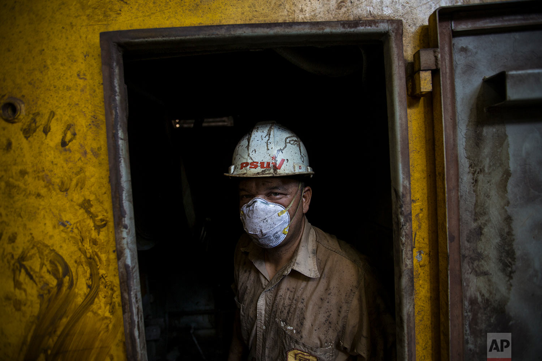 In this Nov. 1, 2017 photo, Juan Carlos Boite repairs a locomotive at Ferrominera Orinoco, in Ciudad Guayana, Bolivar state, Venezuela. In cash-strapped Venezuela, there's no money to buy spare parts. (AP Photo/Rodrigo Abd)