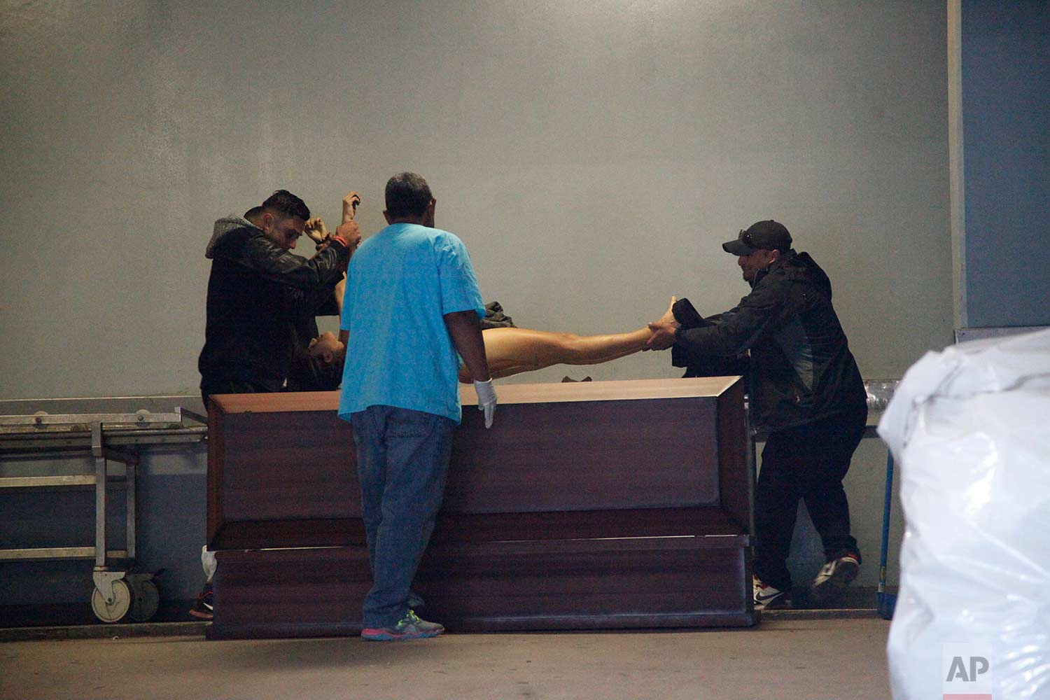 Relatives place the body of Kimberly Dayana Fonseca, 19, in a coffin at a morgue in Tegucigalpa, Honduras, Saturday, Dec. 2, 2017. (AP Photo/Fernando Antonio)
