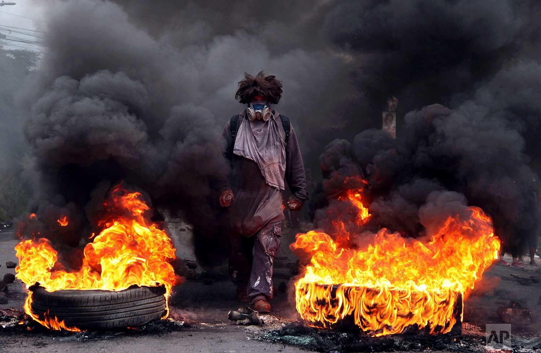 In this Dec. 22, 2017 photo, an anti-government protestor blocks a road, on the outskirts of Tegucigalpa, Honduras. (AP Photo/Fernando Antonio)