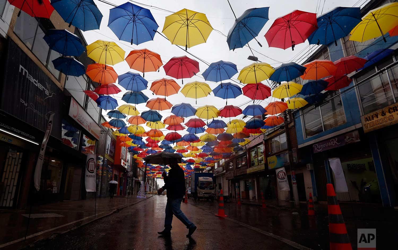 A man walks under a canopy of umbrellas serving as a Christmas decoration, in Bogota, Colombia, Friday, Dec. 1, 2017. (AP Photo/Fernando Vergara)