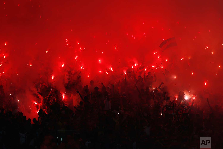 Fans of Brazil's Flamengo soccer team light flares in the stands during a Copa Sudamericana final championship soccer match against Argentina's Independiente at Maracana stadium in Rio de Janeiro, Brazil, Wednesday, Dec.13, 2017. (AP Photo/Silvia Izquierdo)