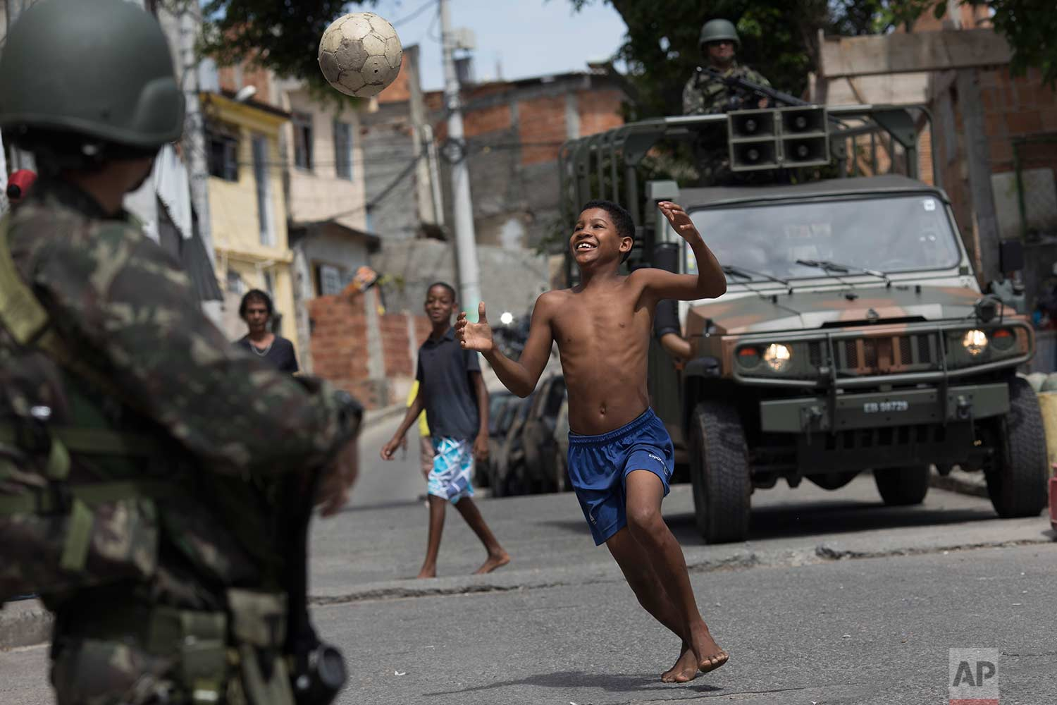 A boy plays soccer next to soldiers on patrol during an operation in the Mangueira slum in Rio de Janeiro, Brazil, Wednesday, Dec. 6, 2017.(AP Photo/Leo Correa)