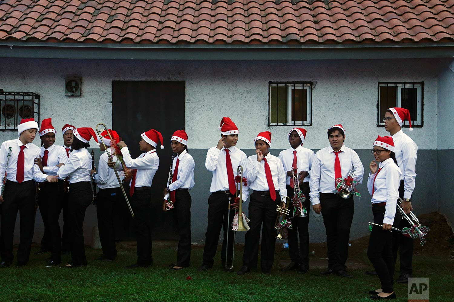 High school student music band members wait to play in the annual Christmas parade in Panama City, Sunday, Dec. 10, 2017. (AP Photo/Arnulfo Franco)