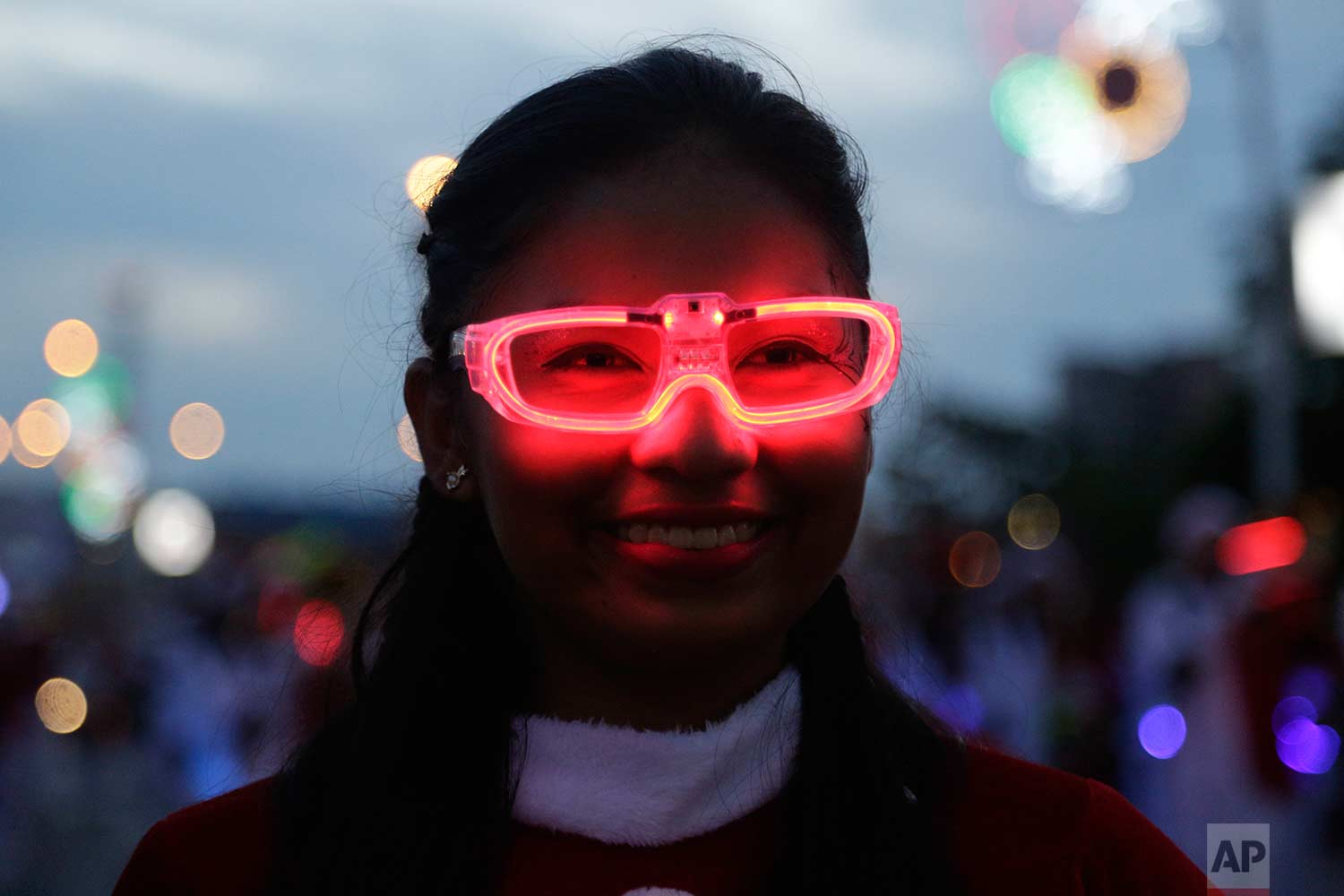 Estefani Garcia wears illuminated glasses as she marches in a music band during the annual Christmas parade in Panama City, Sunday, Dec. 10, 2017. (AP Photo/Arnulfo Franco)