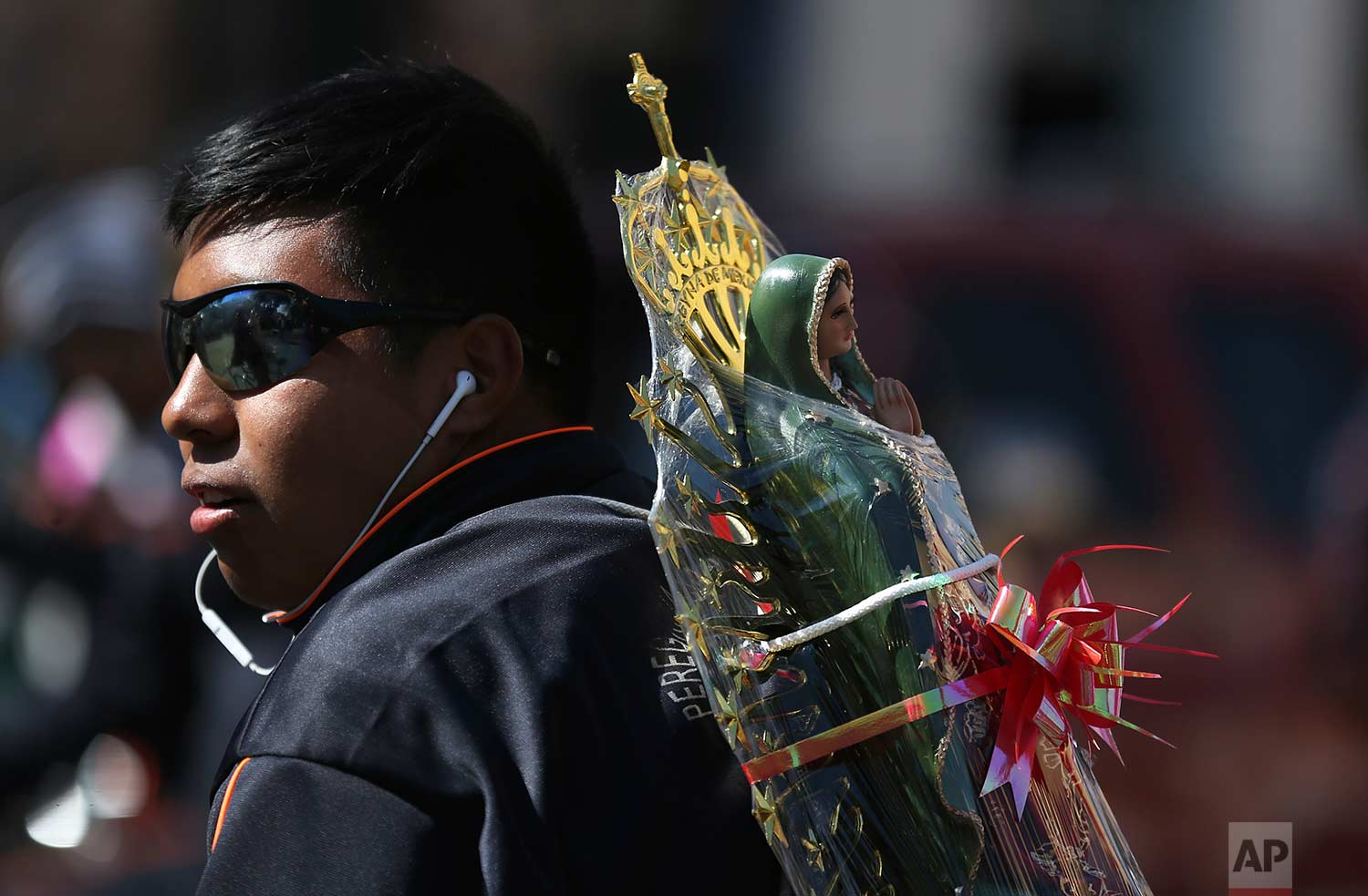 A pilgrim carries on his back a statue of Our Lady of Guadalupe toward the Basilica of the Virgin of Guadalupe in Mexico City, Monday, Dec. 11, 2017. (AP Photo/Marco Ugarte)
