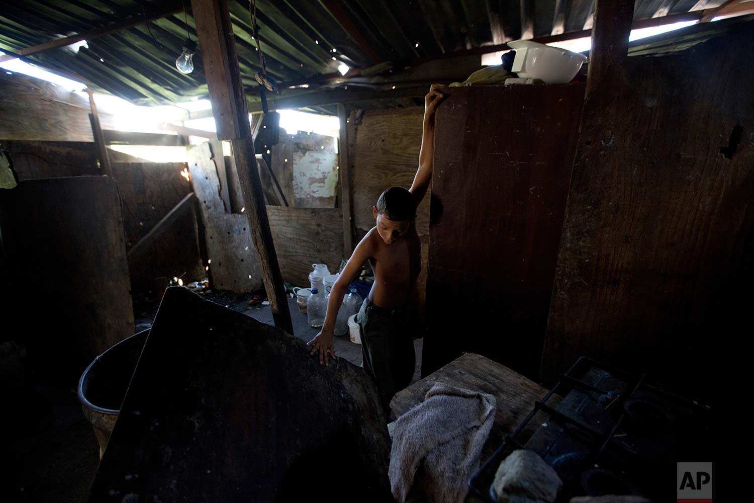 In this Dec. 9, 2017 photo, David Martinez plays inside his home, located in a neighborhood where the opposition set up a free food and medical campaign in La Guaira, Venezuela. (AP Photo/Fernando Llano)