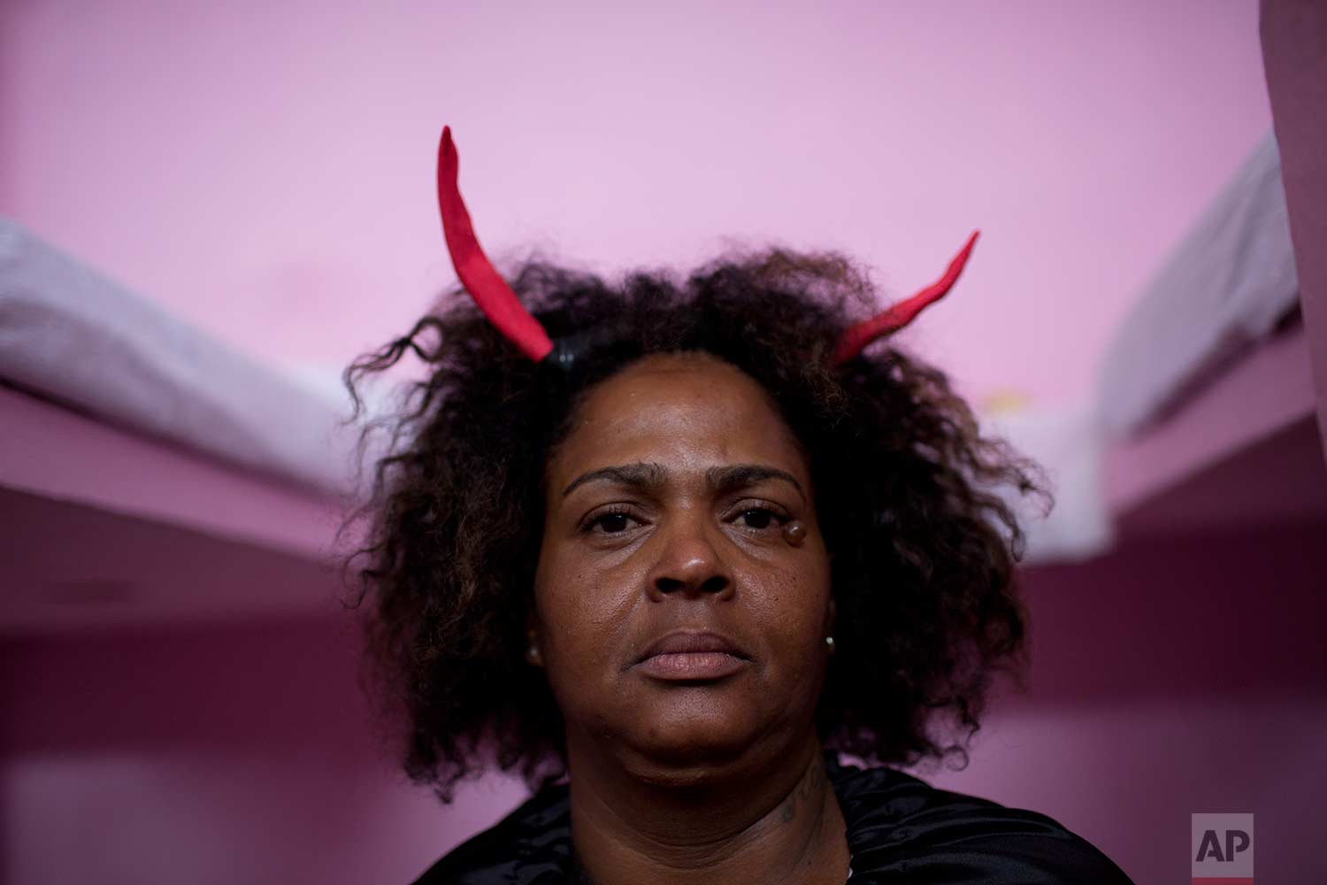 An inmate wears red horns as part of her costume representing evil and temptation, during the 8th annual Christmas event at the Nelson Hungria Prison, in Rio de Janeiro, Brazil, Tuesday, Dec. 12, 2017. (AP Photo/Silvia Izquierdo)