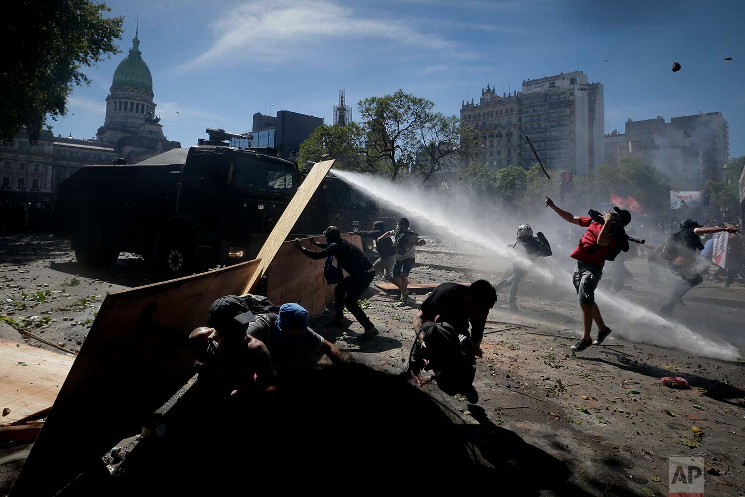 In this Monday, Dec. 18, 2017 photo, protesters clash with police during a general strike against a pension reform measure, outside Congress in Buenos Aires, Argentina.(AP Photo/Victor R. Caivano)