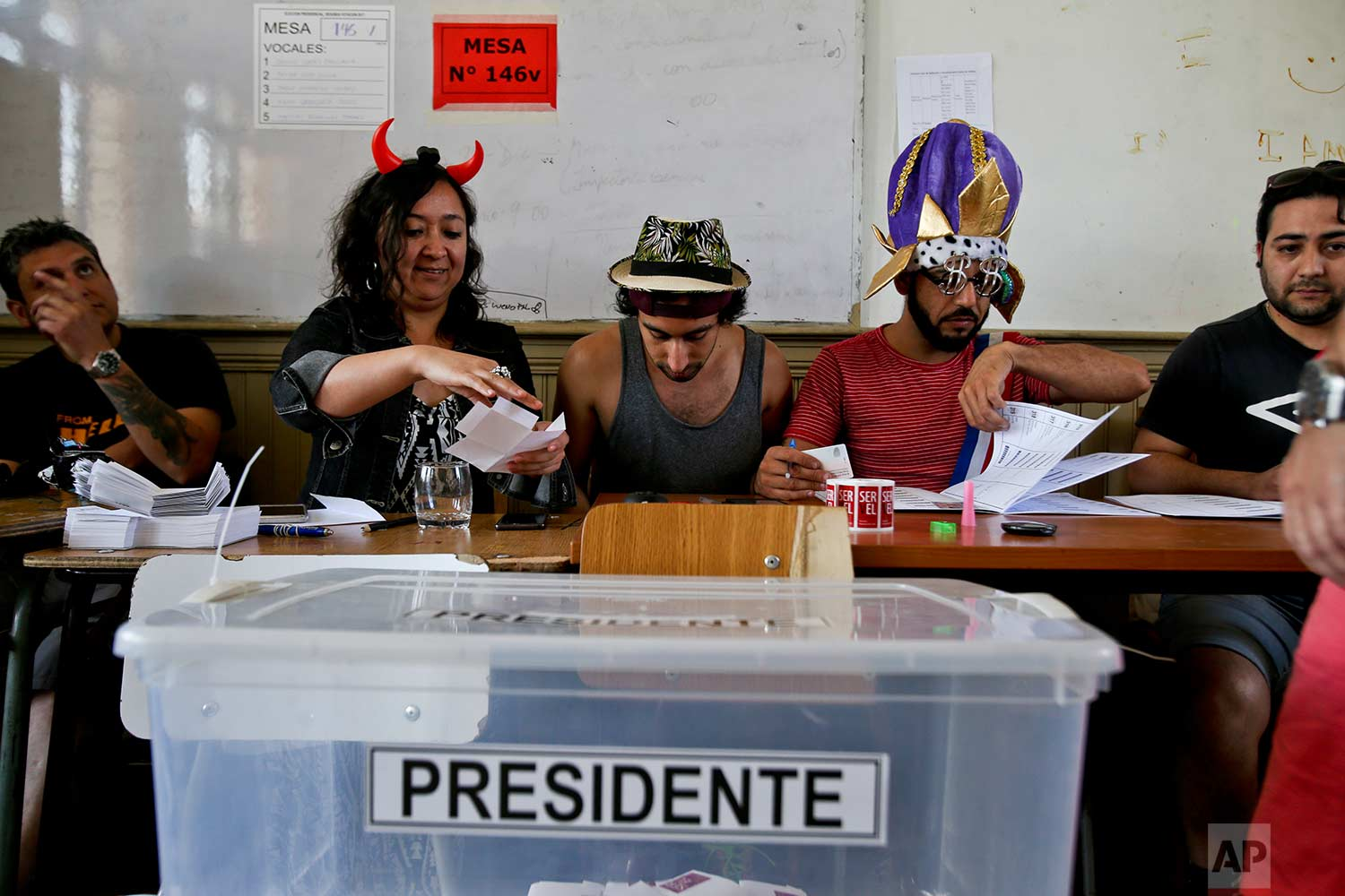 Electoral workers sport costumes during the presidential runoff election in Santiago, Chile, Sunday, Dec. 17, 2017. Chileans will decide Sunday whether to swing the world's top copper-producing country to the right or maintain its center-left path in a fiercely contested election. (AP Photo/Esteban Felix)