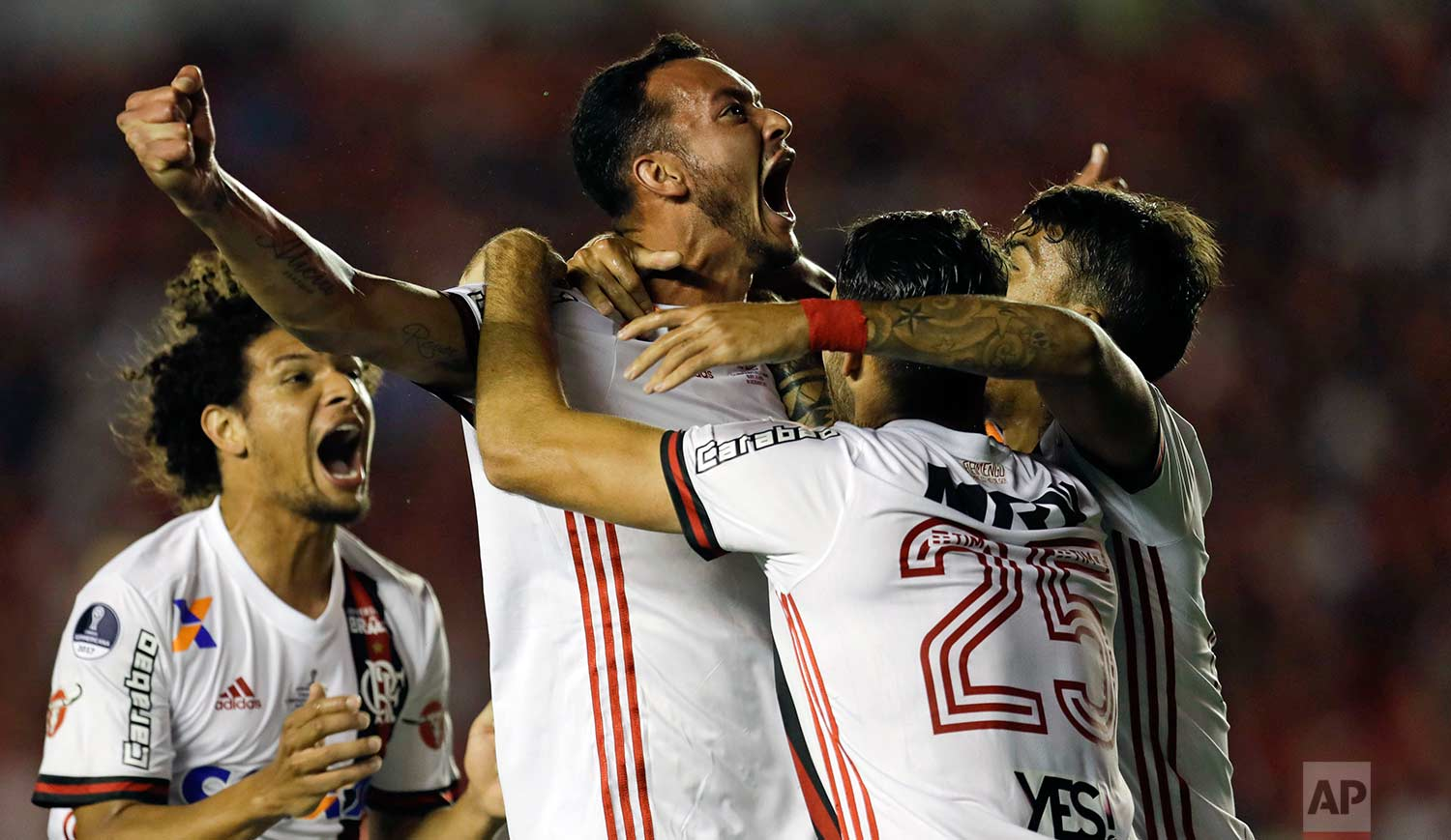In this Wednesday, Dec. 6, 2017 photo, Brazil's Flamengo Rever, center, celebrates his goal against Argentina's Independiente during a Copa Sudamericana first leg, final soccer match in Buenos Aires, Argentina. Independiente went on to win the opening leg 2-1. (AP Photo/Natacha Pisarenko)