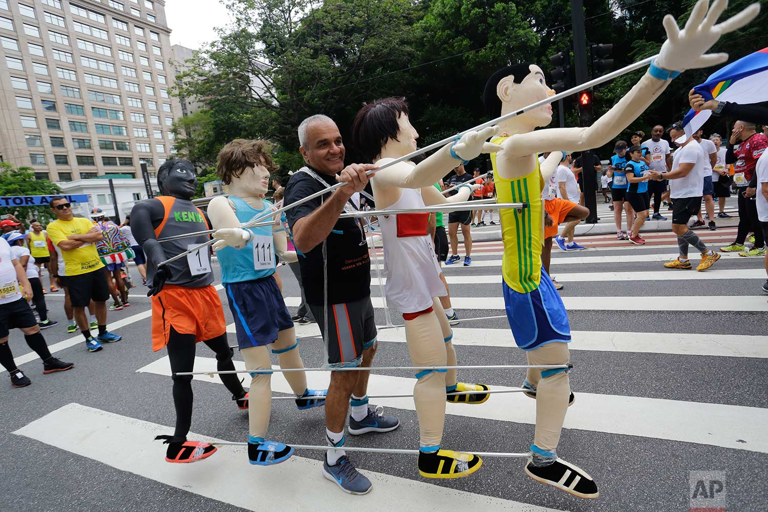 A runner stands with life-size puppets attached to him, prior to the start of the Sao Silvestre race in Sao Paulo, Brazil, early Sunday, Dec. 31, 2017. The 15-kilometer race is held annually on New Year's Eve. (AP Photo/Nelson Antoine)