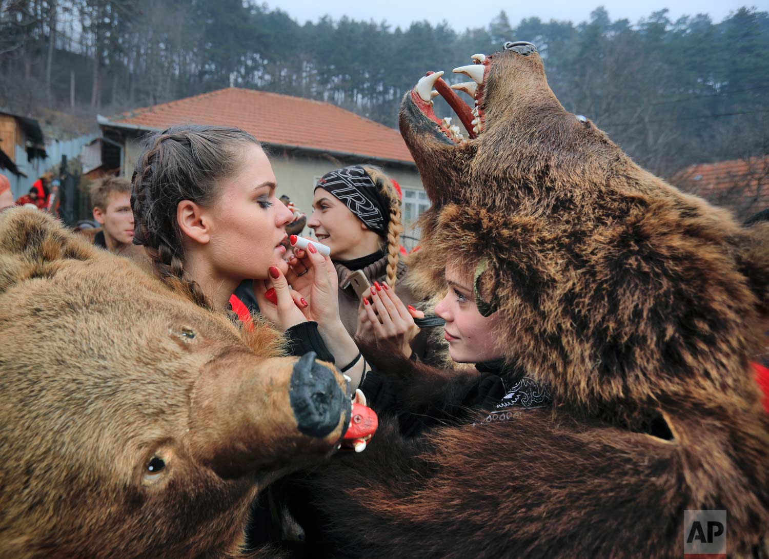 In this Saturday, Dec. 30, 2017, picture Raluca Atrejei, right, helps Roxana Stan, apply lipstick as they get ready for an annual bear parade in Comanesti, Romania. (AP Photo/Vadim Ghirda)