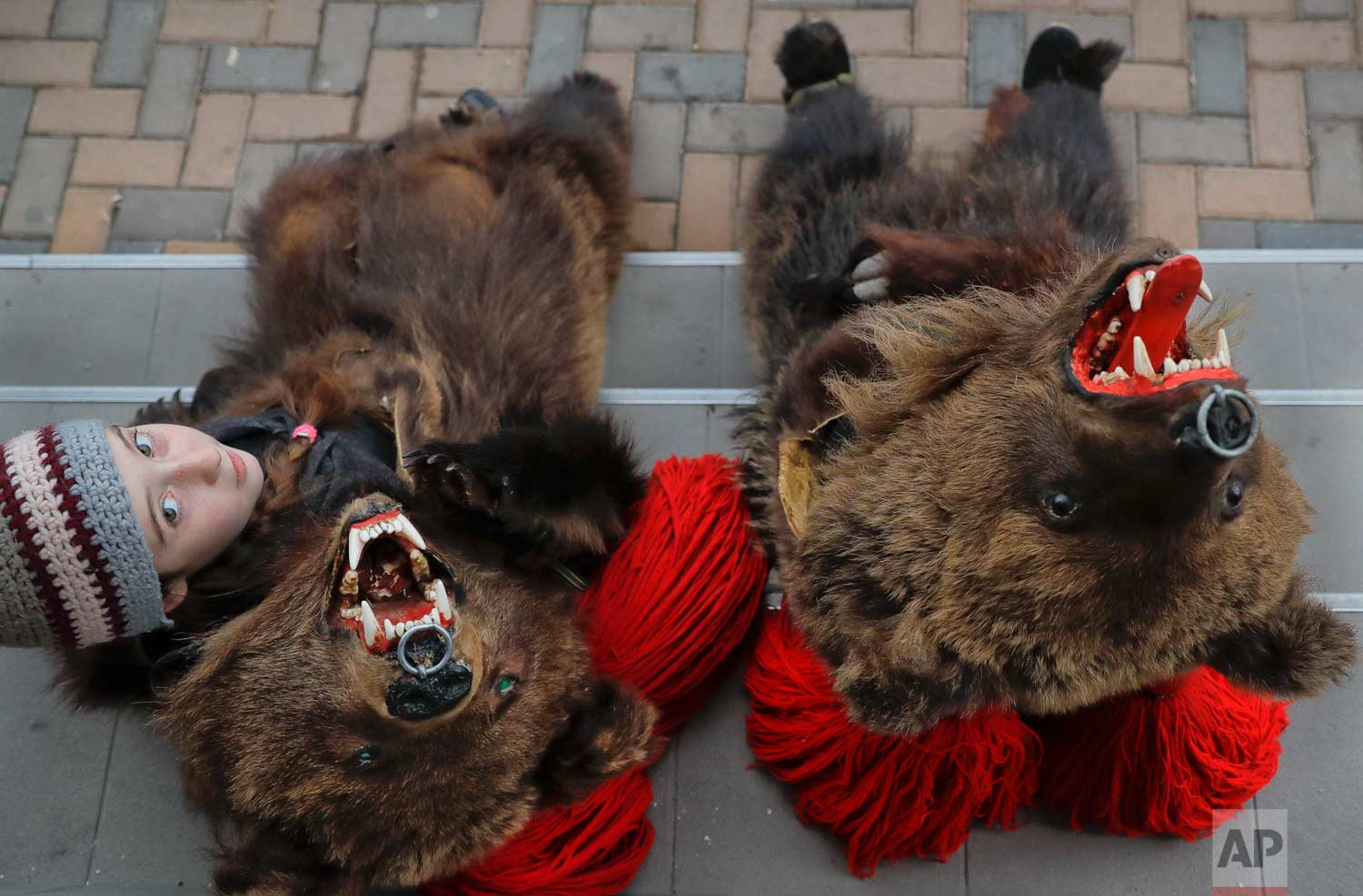 In this Saturday, Dec. 30, 2017, picture, Cleopatra Antonia Turcu, 10 years-old, wearing a bear fur costume pauses next to Georgiana Andresoaie, during an annual bear parade in Comanesti, Romania. (AP Photo/Vadim Ghirda)