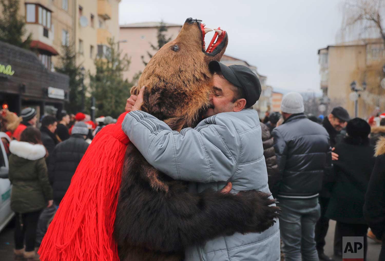 In this Saturday, Dec. 30, 2017, picture men, one wearing a bear fur costume, hug during an annual bear parade in Comanesti, Romania. (AP Photo/Vadim Ghirda)