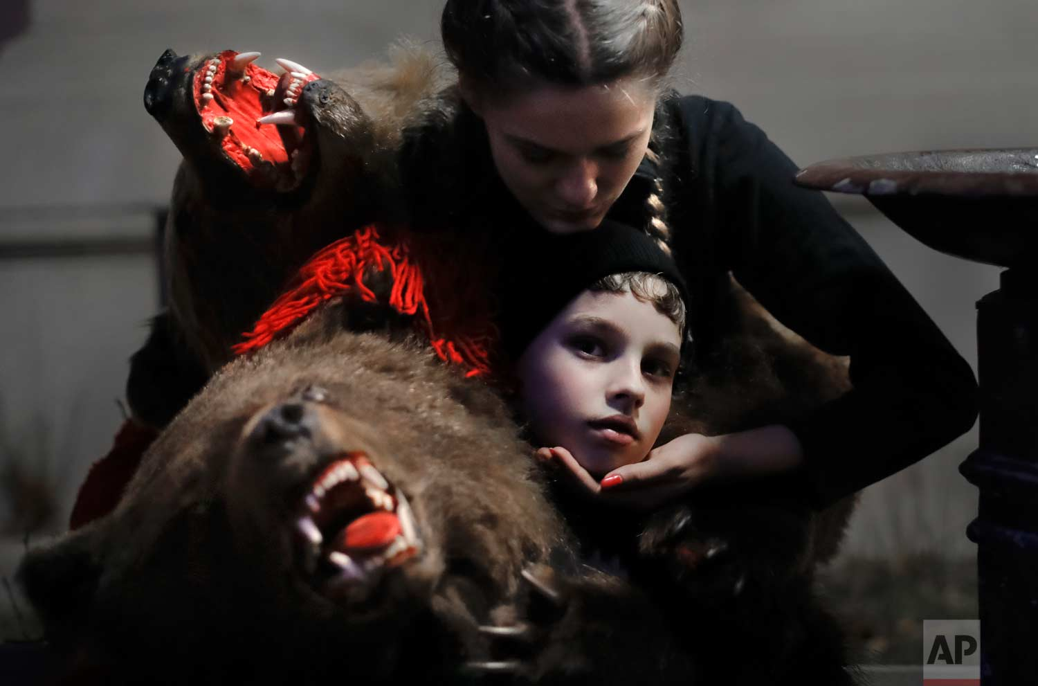 In this Thursday, Dec. 28, 2017, picture Roxana Stan, top, supports 9 year-old Florin Paduceanu as they take a brake from the parade, in Piatra Neamt, Romania. (AP Photo/Vadim Ghirda)