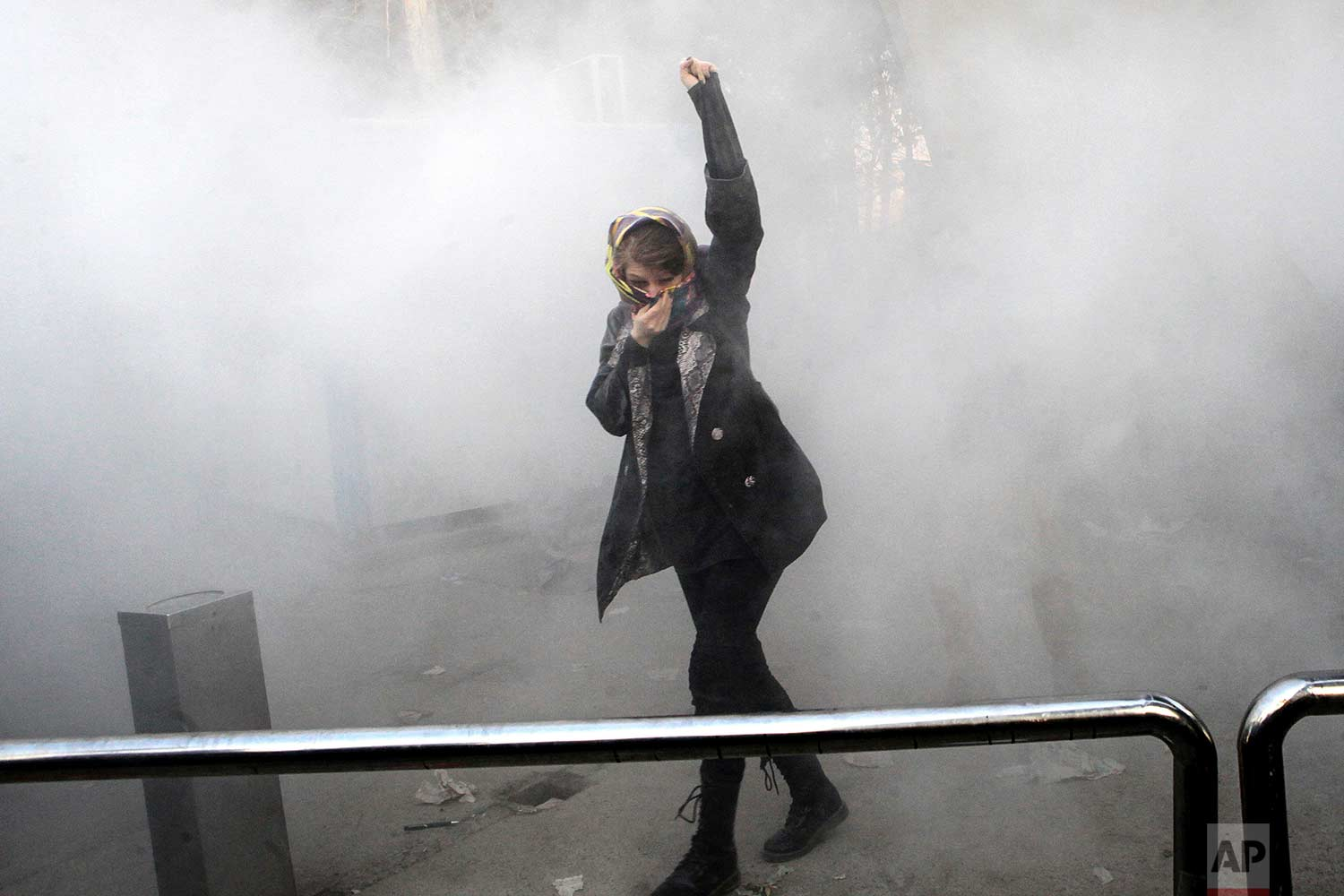 In this Saturday, Dec. 30, 2017 photo made by an individual not employed by the Associated Press and obtained by the AP outside Iran, a university student attends a protest inside Tehran University while a smoke grenade is thrown by Iranian police, in Tehran, Iran. (AP Photo)