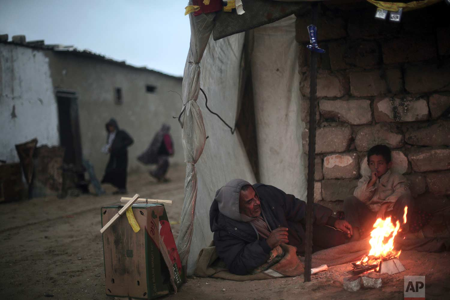 A Palestinian man and his son warm themselves by a fire during cold, rainy weather in a slum on the outskirts of the Khan Younis refugee camp, southern Gaza Strip, Friday, Jan. 5, 2018. (AP Photo/Khalil Hamra)