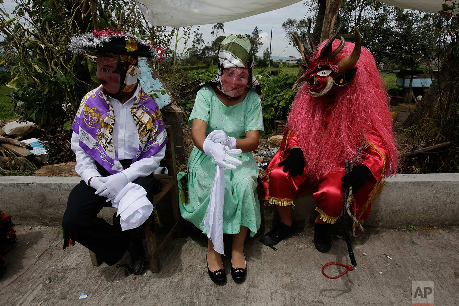 "People dressed in costumes take a break during the traditional New Year's festival known as ""La Diablada"", in Pillaro, Ecuador, Friday, Jan. 5, 2018. (AP Photo/Dolores Ochoa)"