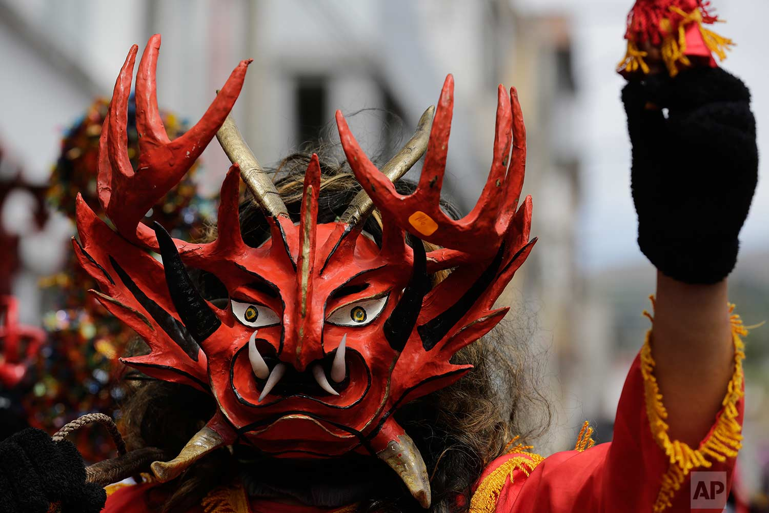 "A man wearing a devil mask takes part in a parade as part of the traditional New Year's festival known as ""La Diablada"", in Pillaro, Ecuador, Friday, Jan. 5, 2018. (AP Photo/Dolores Ochoa)"