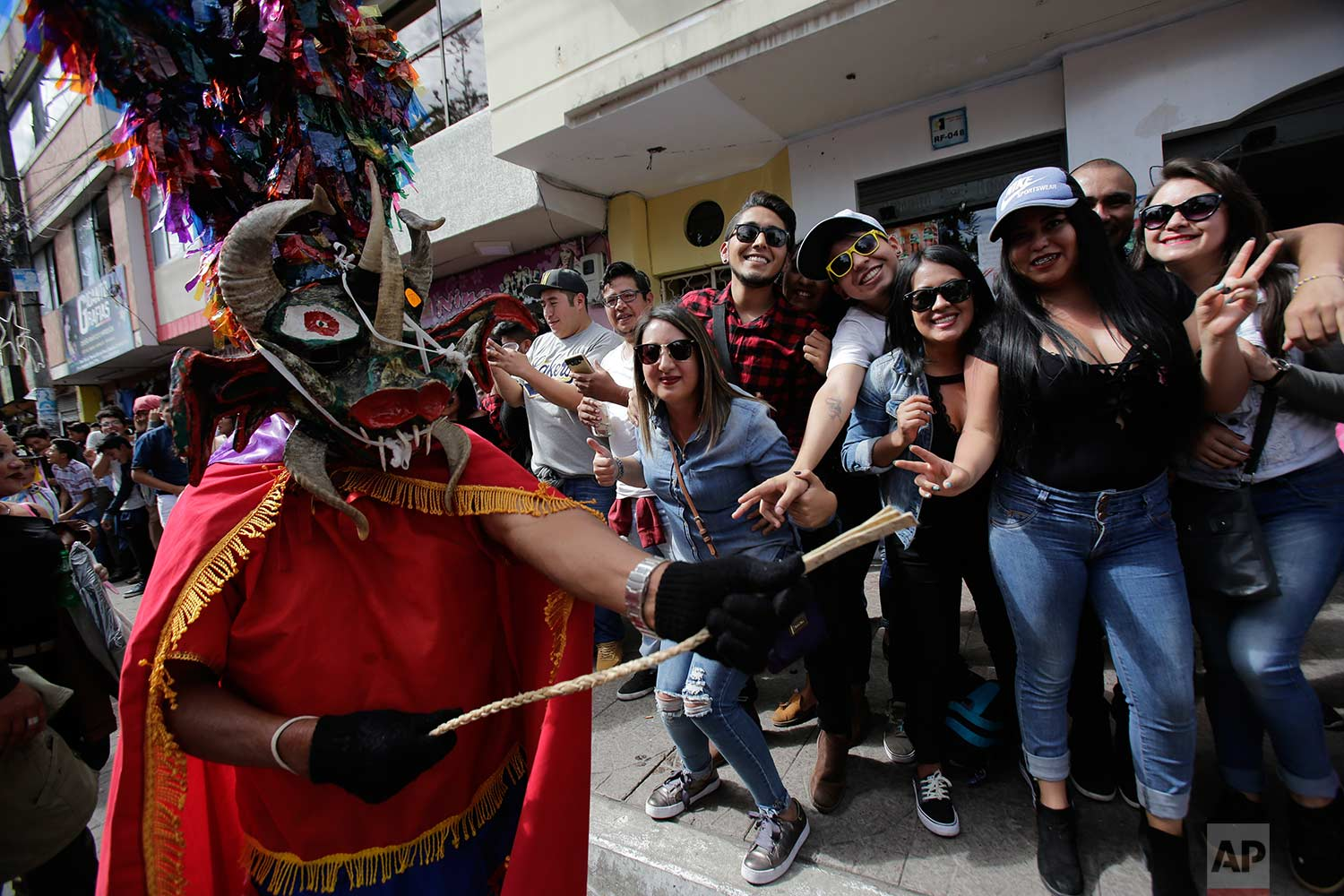 "Revelers watch as people dressed as devils parade past during the traditional New Year's festival known as ""La Diablada"", in Pillaro, Ecuador, Friday, Jan. 5, 2018. (AP Photo/Dolores Ochoa)"