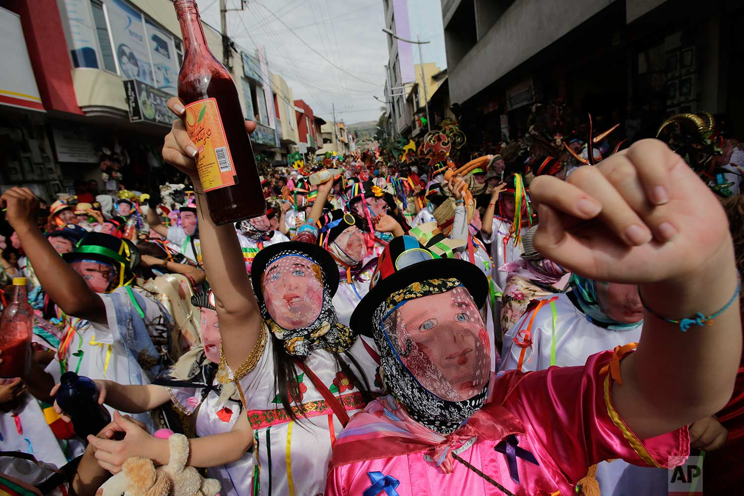 "Revelers wear wire mesh mask that represent the more affluent during the traditional New Year's festival known as ""La Diablada"", in Pillaro, Ecuador, Friday, Jan. 5, 2018. (AP Photo/Dolores Ochoa)"