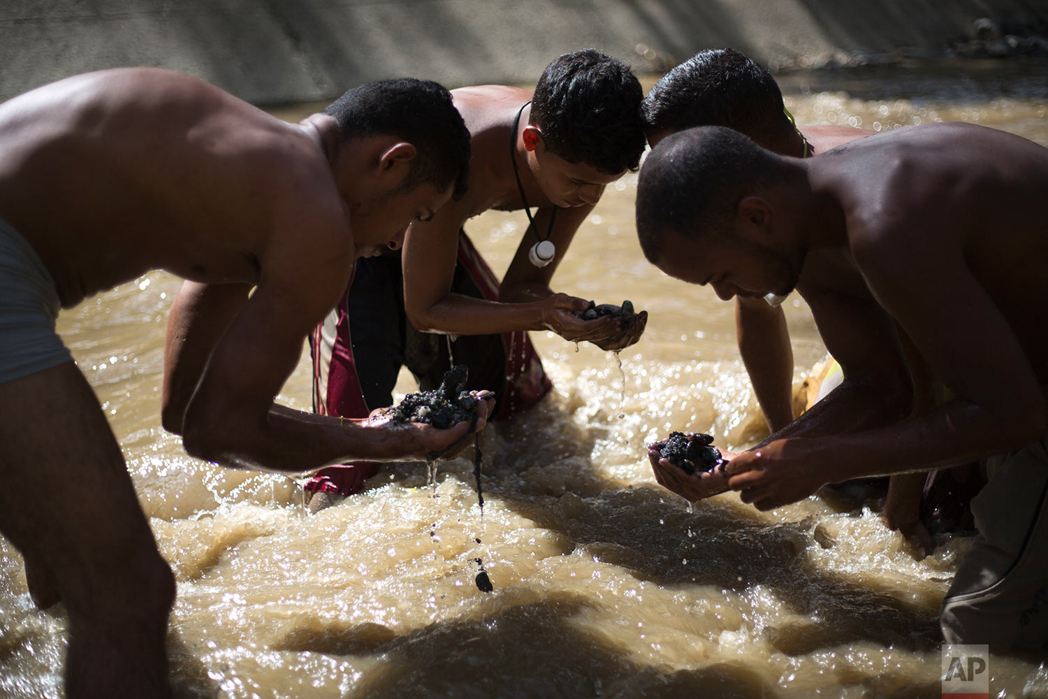 In this Dec. 5, 2017 photo, Angel Villanueva, right, looks for pieces of gold and other valuables in the debris he scooped up from the bottom of the polluted Guaire River, alongside other scavengers, in Caracas, Venezuela. As the 25-year-old scavenges alongside his friends, he's mindful that flash flooding leaves just minutes to get out, or be washed away to his death. Villanueva said he buys food with the money he earns that comes from selling what he finds in the river. (AP Photo/Ariana Cubillos)