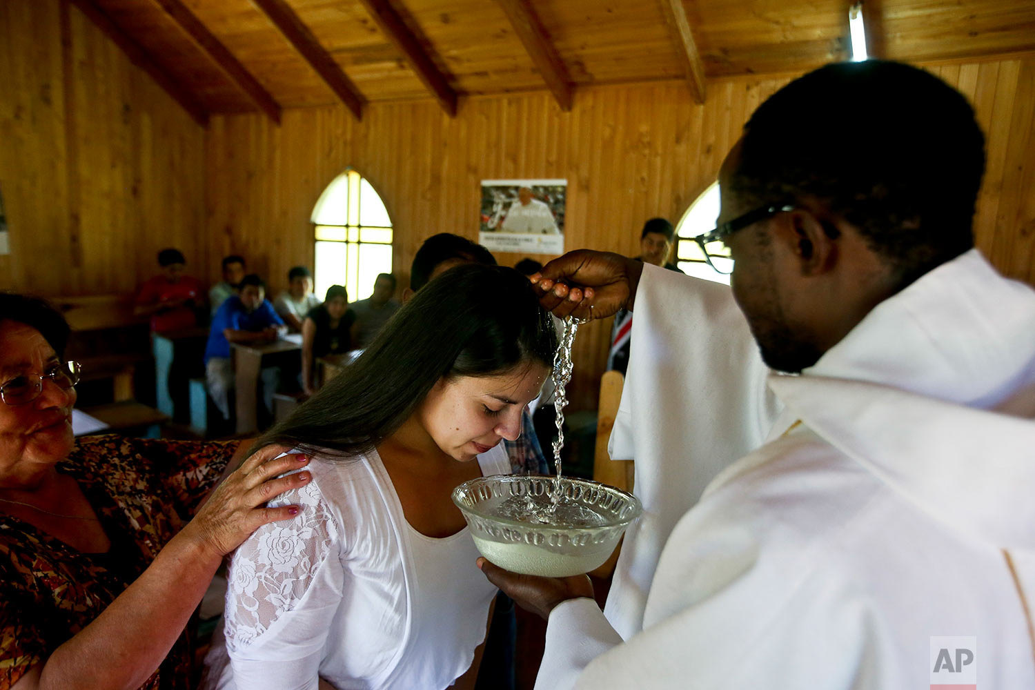 In this Sunday, Jan. 7, 2018 photo, Priest Claude Yves Dilayen baptizes a woman in the Mapuche community Newen Wenu Chau in Temuco, Chile, Sunday, Jan. 7, 2018.(AP Photo/Esteban Felix) |  See these photos on AP Images