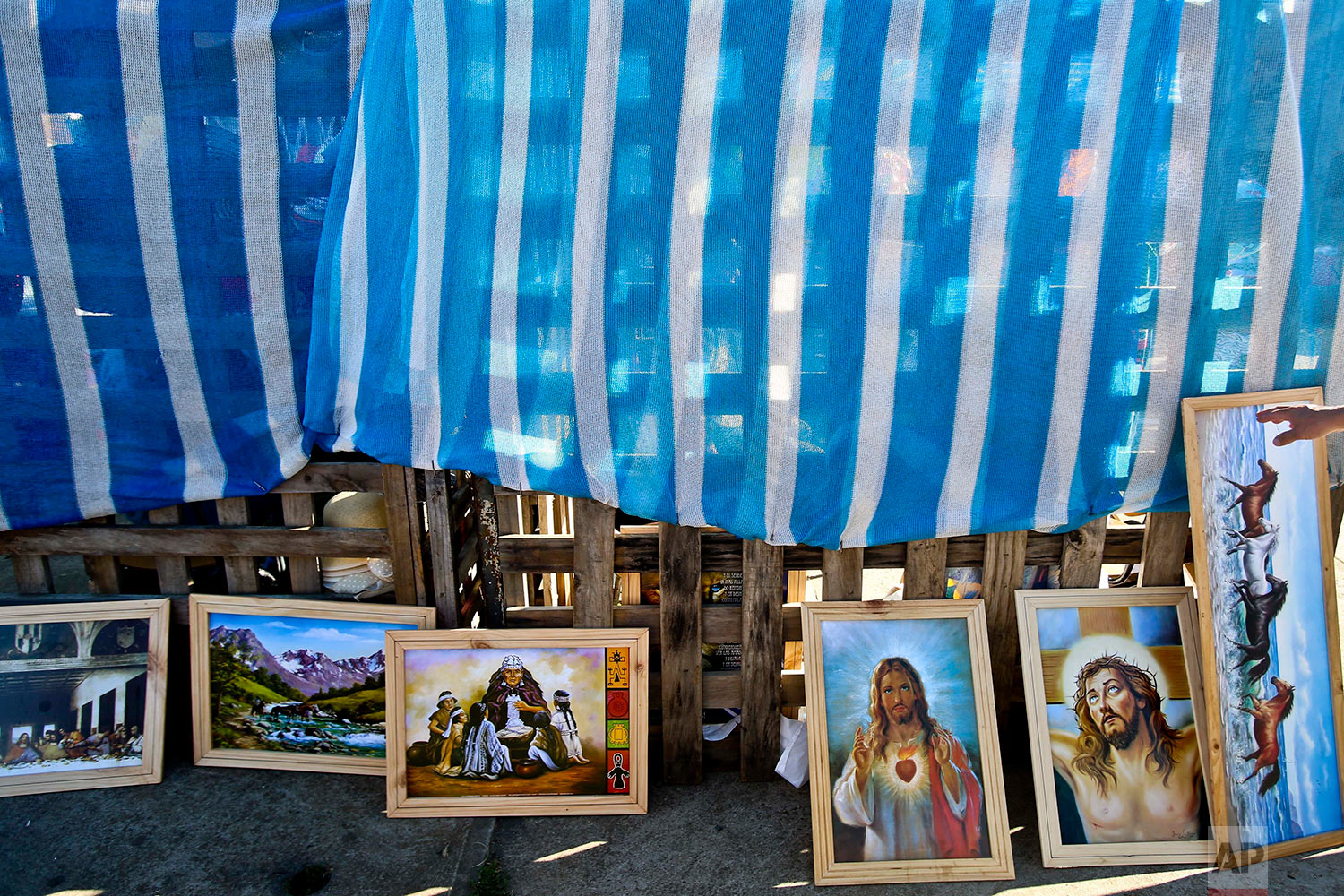This Jan. 7, 2018 photo shows paintings with Mapuche, Catholic and scenic motifs displayed for sale at a cultural fair in the Puerto Dominguez community in Temuco, Chile. (AP Photo/Esteban Felix) | See these photos on AP Images