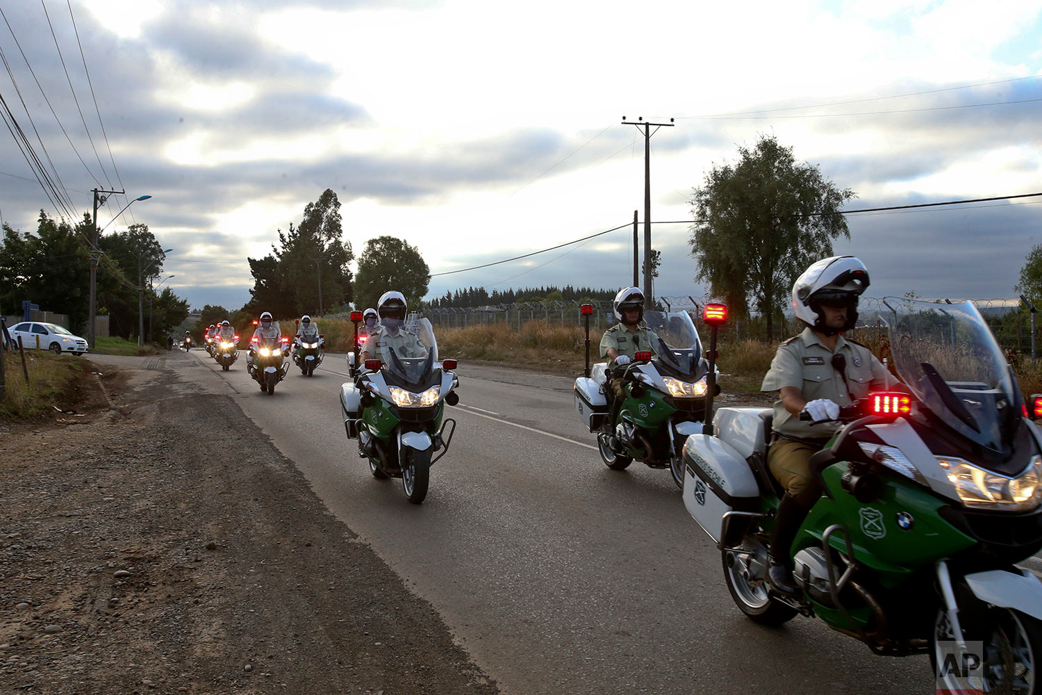 In this Monday, Jan. 8, 2018 photo, Chilean police drive past the Maquehue Air Base, the air base where Pope Francis will celebrate Mass in Temuco, Chile. Chilean authorities plan to deploy more than 4,000 police officers in Temuco's streets. Flanked by 16 police vehicles, Francis will ride in the pope mobile down a central avenue before visiting an order of nuns. (AP Photo/Esteban Felix) | See these photos on AP Images