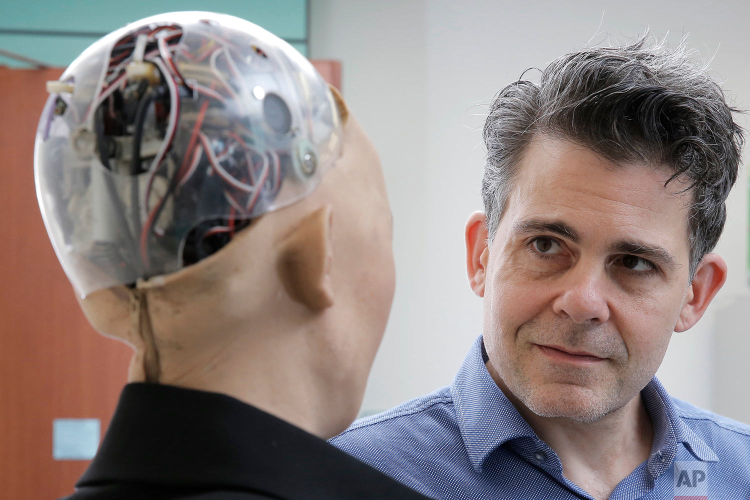 In this Sept. 28, 2017 photo, the founder of Hanson Robotics, David Hanson, right, chats with his company's flagship robot Sophia, a lifelike robot powered by artificial intelligence (AI) in Hong Kong. (AP Photo/Kin Cheung) |  See these photos on AP Images