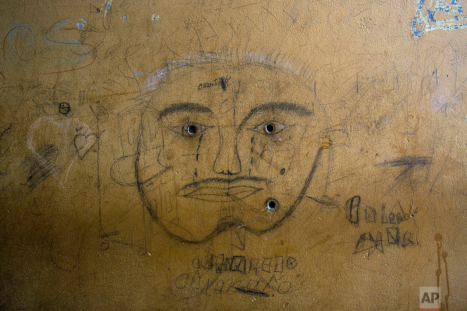 """In this Jan. 12, 2018 photo, writings and a drawing cover the wall of the carpentry workshop at a prison where inmates are building chairs that will be used by indigenous leaders during events with Pope Francis in Puerto Maldonado, Madre de Dios province, Peru. """"We are paying for the bad we did,"""" said Sergio Curay, 48, who is serving nine years for aggravated robbery. """"We hope the pope will forgive us."""" (AP Photo/Rodrigo Abd)