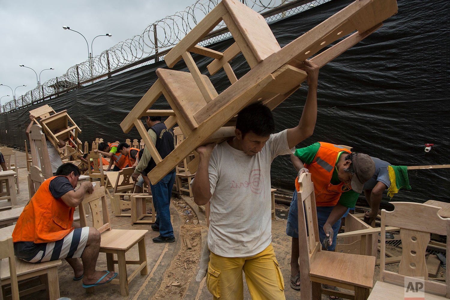 In this Jan. 12, 2018 photo, inmates build the chairs that will be used during events with Pope Francis in Puerto Maldonado, Madre de Dios province, Peru. Prisoners convicted of crimes like robbery and drug trafficking at the prison in the Peruvian Amazon are using their time behind bars to build simple wooden chairs that indigenous leaders will use while meeting with Pope Francis. (AP Photo/Rodrigo Abd)| See these photos on AP Images