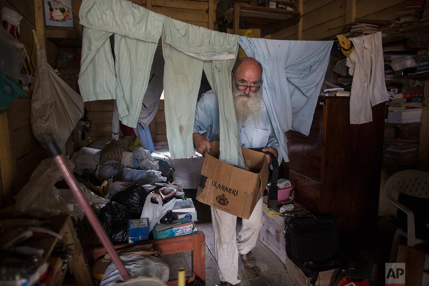 In this Jan. 11, 2018 photo, Father Pablo Zabala, better known as Padre Pablo, cleans up the sleeping quarters where he resides in Boca Colorado, part of Peru's Madre de Dios region in the Amazon. The 70-year-old Spanish priest first traveled to the Amazon in 1978 when, as a young biologist, he collected butterflies and condors for his university's museum in Spain. (AP Photo/Rodrigo Abd) |  See these photos on AP Images
