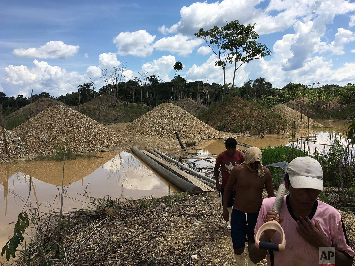 In this Jan. 9, 2018 photo, illegal gold miners walk in a mining camp in Boca Colorado, part of Peru's Madre de Dios province in the Amazon. It's near this forlorn corner of the Amazon that Pope Francis will visit Friday, Jan. 19, amid what has been called a modern-day gold rush of illegal miners threatening the world's largest rainforest. (AP Photo/Rodrigo Abd) |  See these photos on AP Images