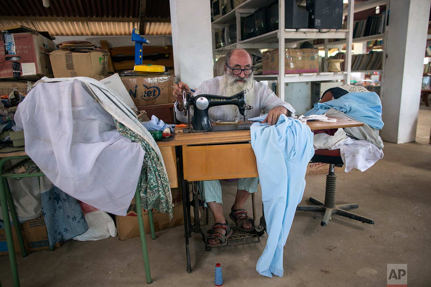 In this Jan. 13, 2018 photo, Father Pablo Zabala, better known as Padre Pablo, sews himself a new pair of pajamas at the parish in Boca Colorado, part of Peru's Madre de Dios province in the Amazon. Known for his eccentric style, the 70-year-old Spanish priest often celebrates Mass barefoot, and when not in his cassock can be seen wearing lightweight sleepwear, an outfit he says is ideal for the humid Amazon climate. (AP Photo/Rodrigo Abd) |  See these photos on AP Images