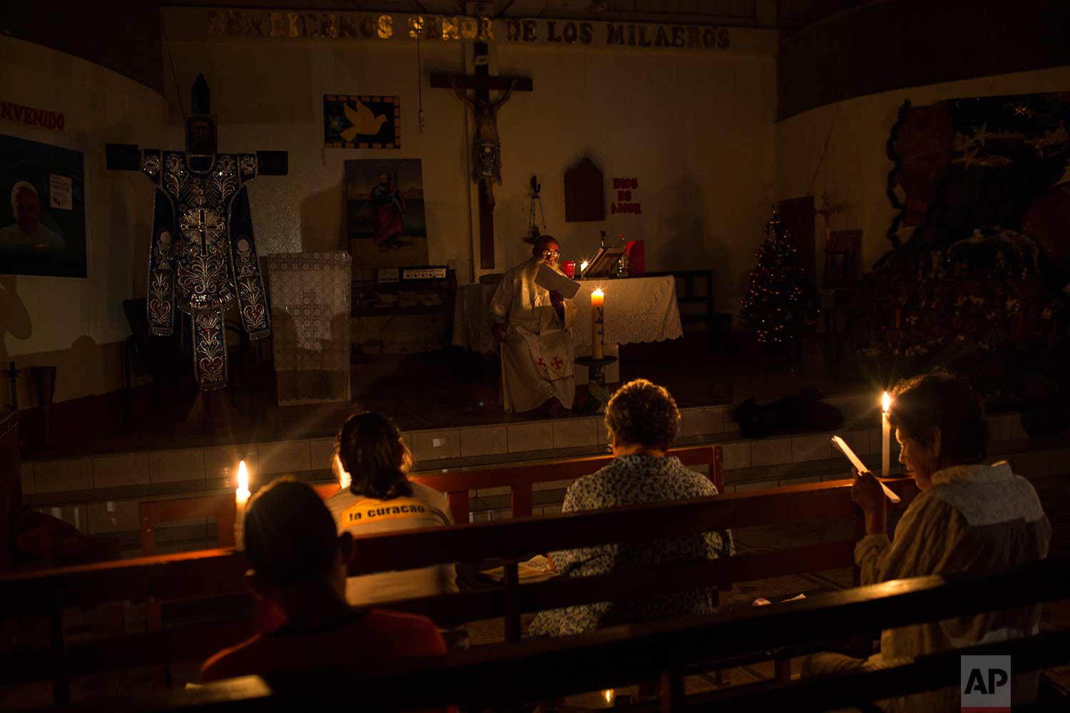 In this Jan. 8, 2018 photo, Father Pablo Zabala, better known as Padre Pablo, celebrates Mass illuminated by candlelight at a church in Boca Colorado, part of Peru's Madre de Dios region in the Amazon. The town was experiencing a power outage that lasted more than 30 hours. (AP Photo/Rodrigo Abd) |  See these photos on AP Images