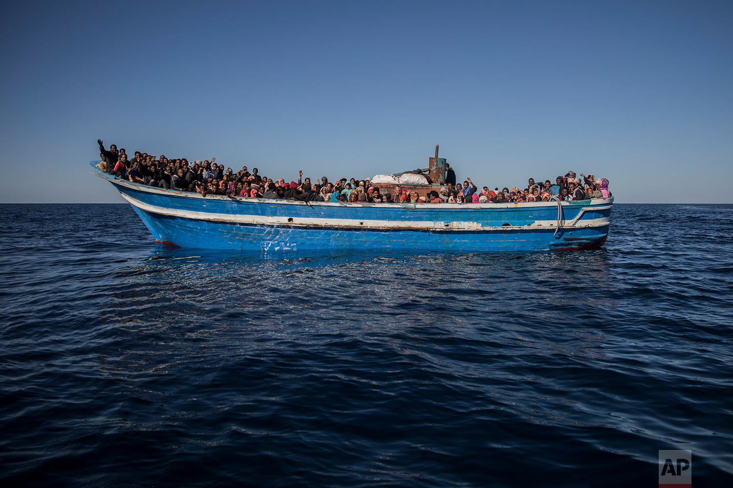 In this Tuesday, Jan. 16, 2018, photo, about 450 Sub-Saharan refugees and migrants, mostly from Eritrea, wait to be rescued by aid workers of Spanish NGO Proactiva Open Arms, as they were trying to leave the Libyan coast and reach European soil aboard an overcrowded wooden boat, 34 miles north of Kasr-El-Karabulli, Libya. (AP Photo/Santi Palacios)