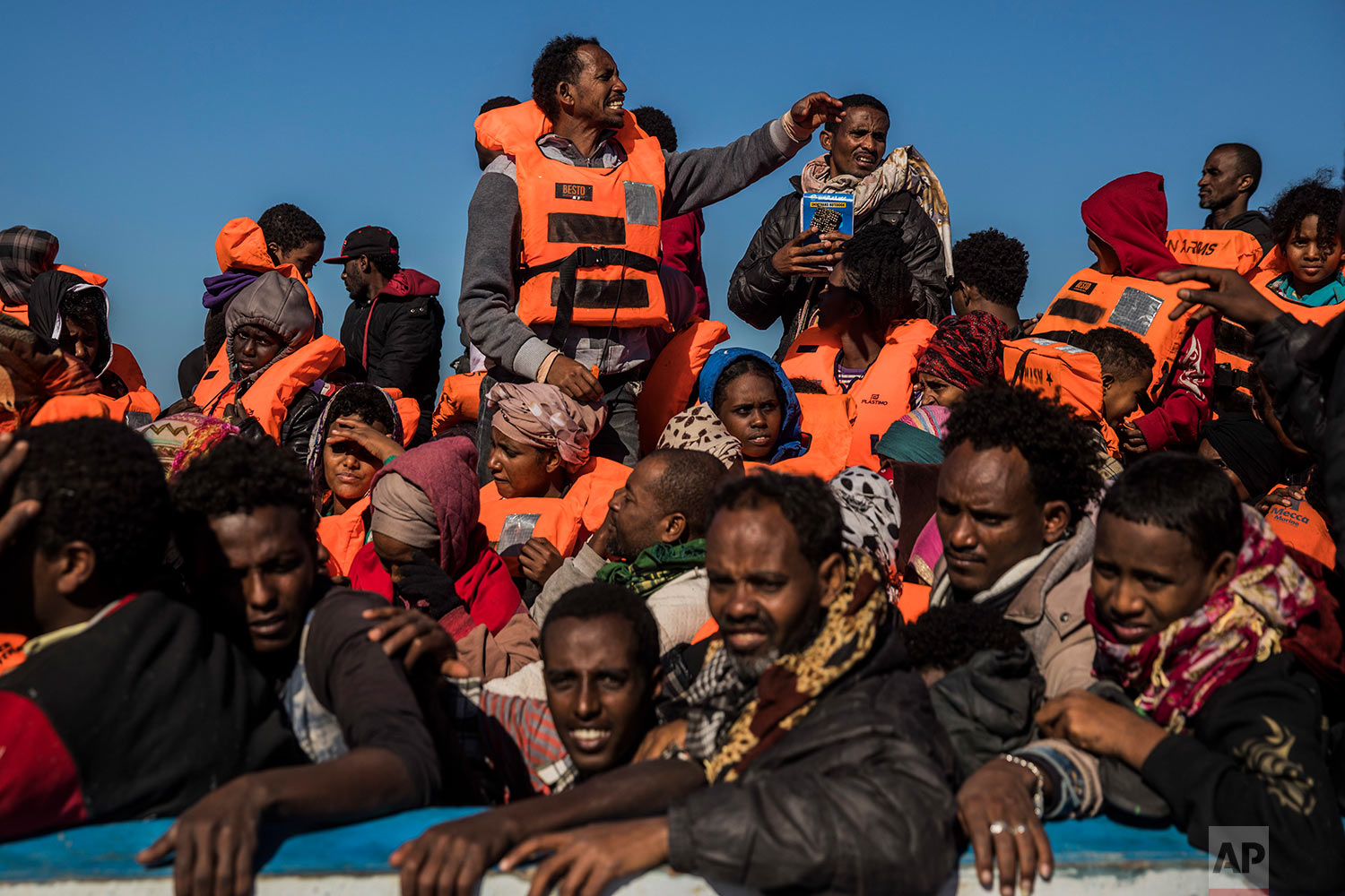 In this Tuesday, Jan. 16, 2018 photo, about 450 Sub-Saharan refugees and migrants, mostly from Eritrea, wait to be rescued by aid workers of Spanish NGO Proactiva Open Arms, as they were trying to leave the Libyan coast and reach European soil aboard an overcrowded wooden boat, 34 miles north of Kasr-El-Karabulli, Libya. (AP Photo/Santi Palacios)
