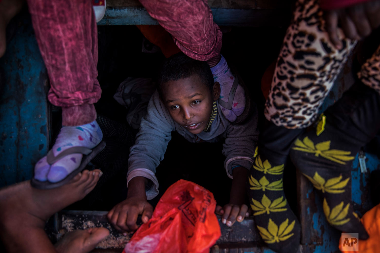 In this Tuesday, Jan. 16, 2018 photo a boy from Eritrea tries to leave the lower deck of a wooden boat with 450 people on aboard, as they were trying to leave the Libyan coast and reach European soil, 34 miles north of Kasr-El-Karabulli, Libya. (AP Photo/Santi Palacios)