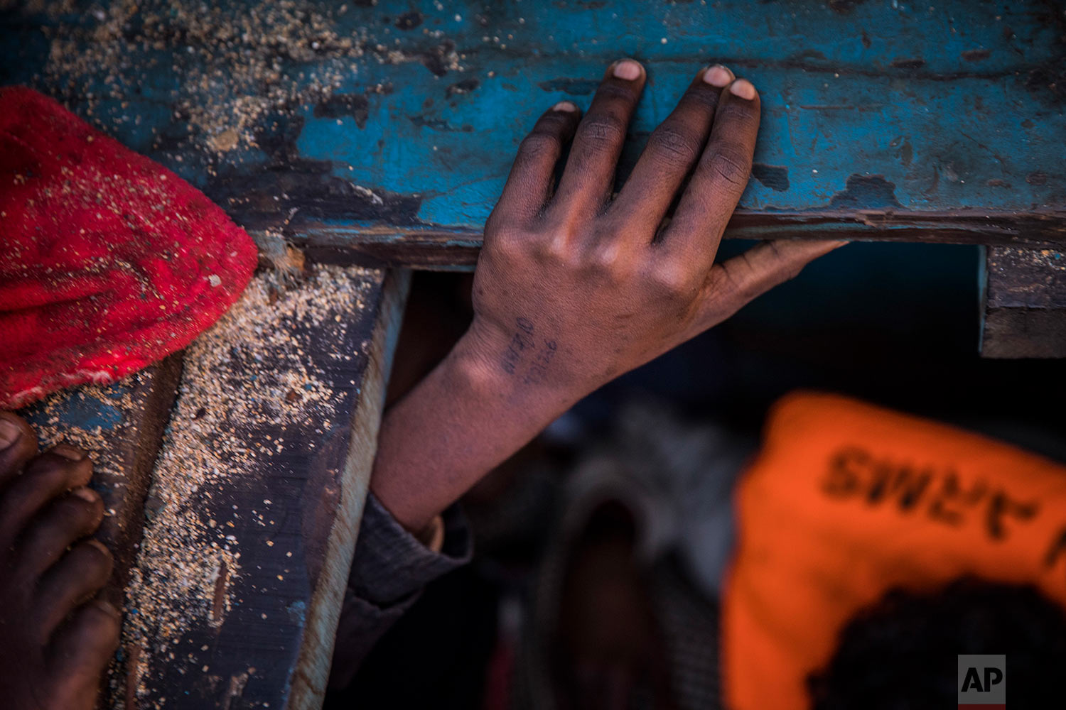 In this Tuesday, Jan. 16, 2018 photo, a boy from Eritrea tries to leave the lower deck of a wooden boat with 450 people on board, as they were trying to leave the Libyan coast and reach European soil, 34 miles north of Kasr-El-Karabulli, Libya. (AP Photo/Santi Palacios)