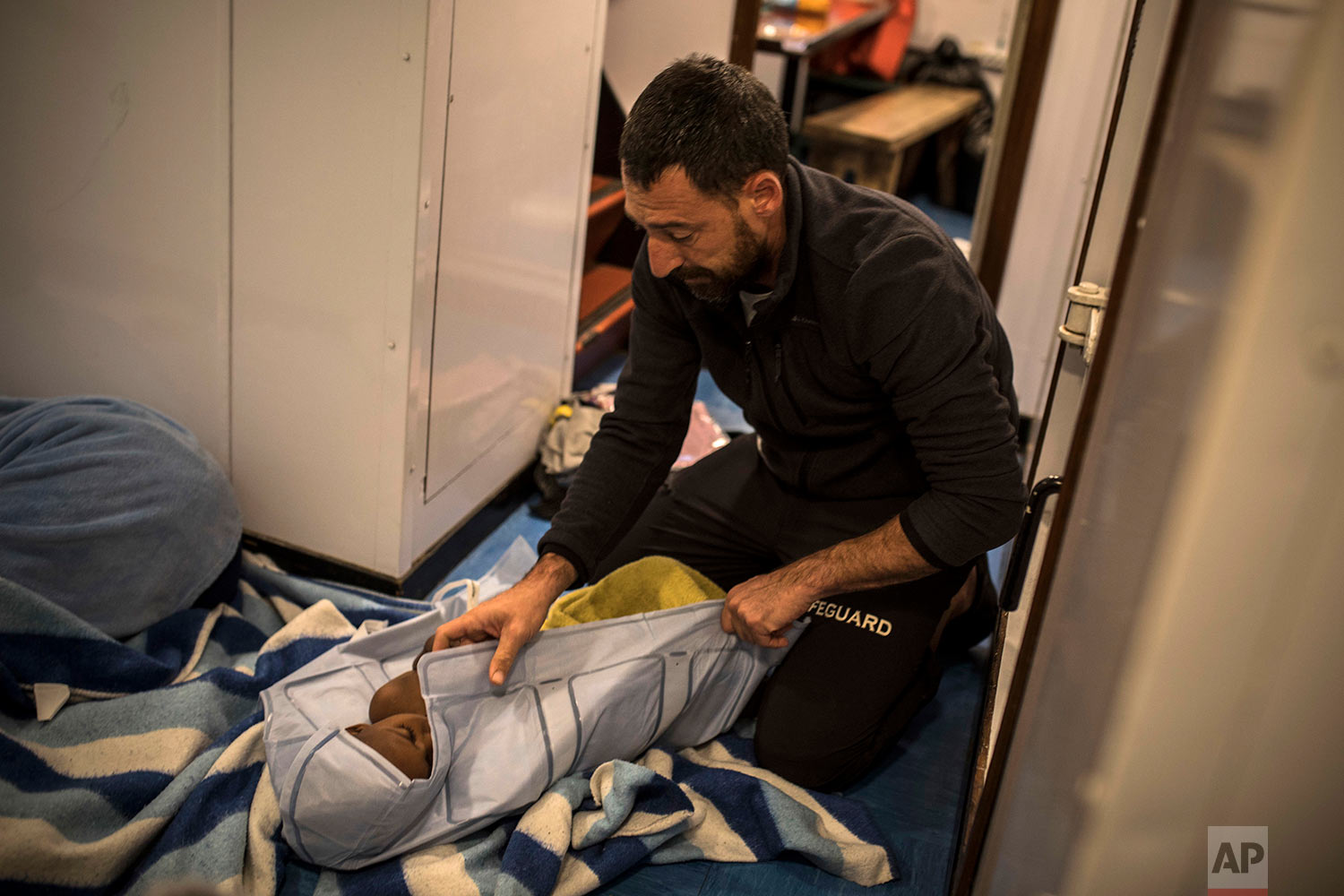 In this Thursday, Jan. 18, 2018 photo Guillermo Cañardo, a doctor from the Spanish NGO Proactiva Open Arms, assists an Eritrean child as the organization's rescue vessel heads to Italy with more than 500 refugees and migrants on board. (AP Photo/Santi Palacios)