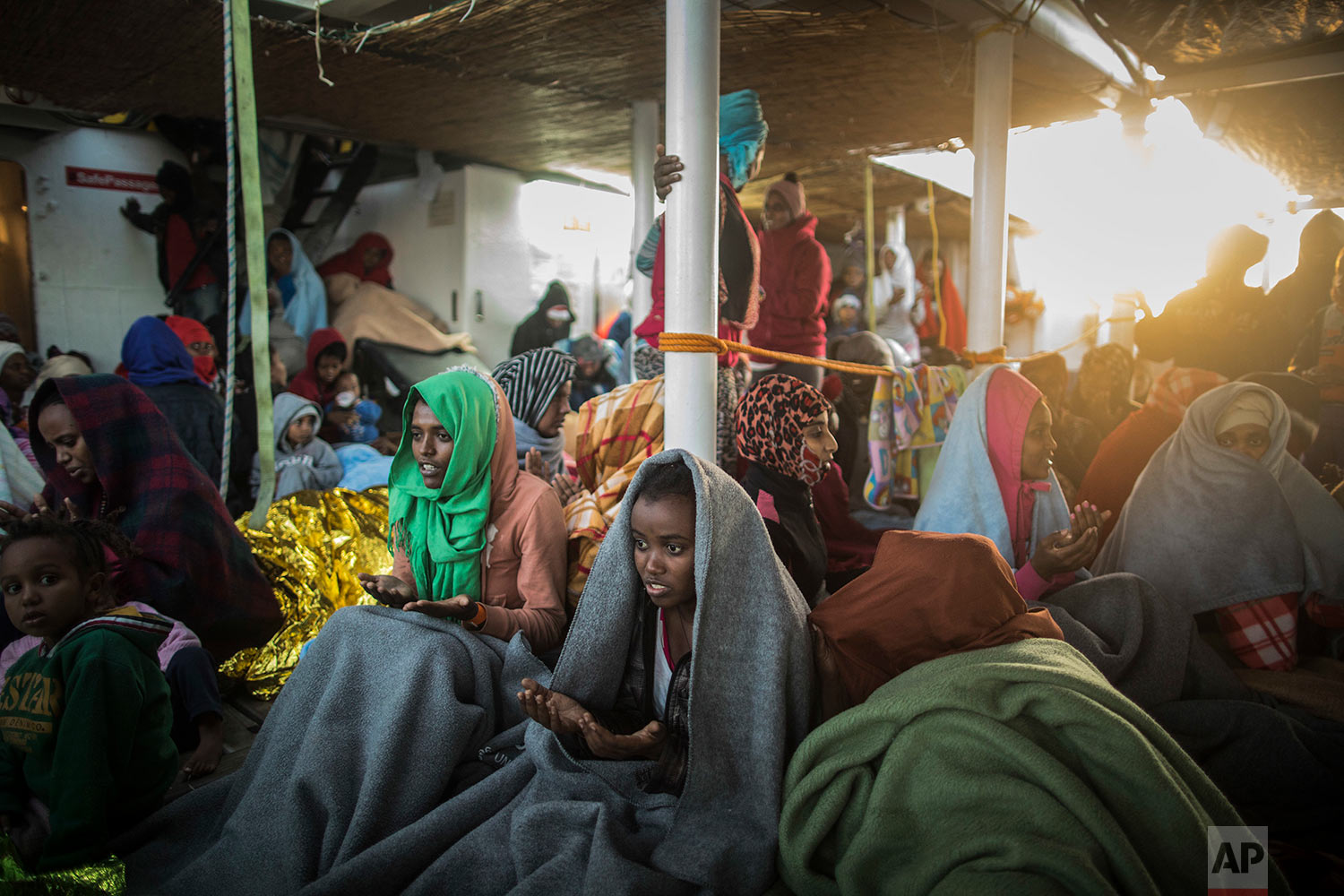 In this Friday, Jan. 19, 2018 photo women and children from Eritrea sing and pray to celebrate their arrival to Europe aboard the Spanish NGO Proactiva Open Arms rescue vessel, Pozzallo, Sicily, Italy. (AP Photo/Santi Palacios)