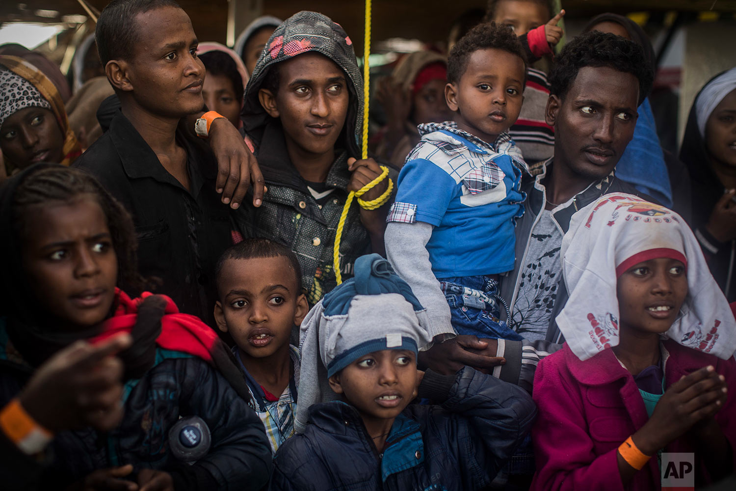 In this Friday, Jan. 19, 2018 photo Sub-Saharan refugees and migrants look to the Italian authorities from aboard the Spanish NGO Proactiva Open Arms rescue vessel, at the port of Pozzallo, in Sicily, Italy. (AP Photo/Santi Palacios)
