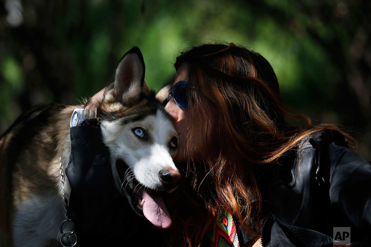 In this Wednesday, Dec. 24, 2017 photo, Mariam Gutierrez de Velasco nuzzles with her dog Ash during a trip to Chapultepec forest in Mexico City. Mariam loves her dogs so much that she considers them her children. (AP Photo/Marco Ugarte)