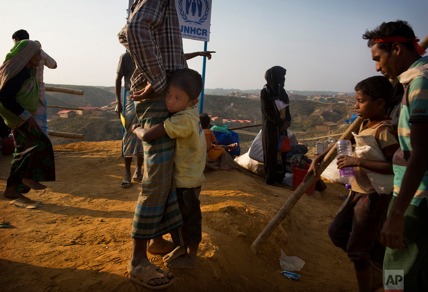 A Rohingya refugee boy who was staying in no-man's land at Bandarban between Myanmar and Bangladesh border, clings to his father after arriving at Balukhali refugee camp 50 kilometres (32 miles) from, Cox's Bazar, Bangladesh Wednesday, Jan. 24, 2018. (AP Photo/Manish Swarup)   See these photos on AP Images