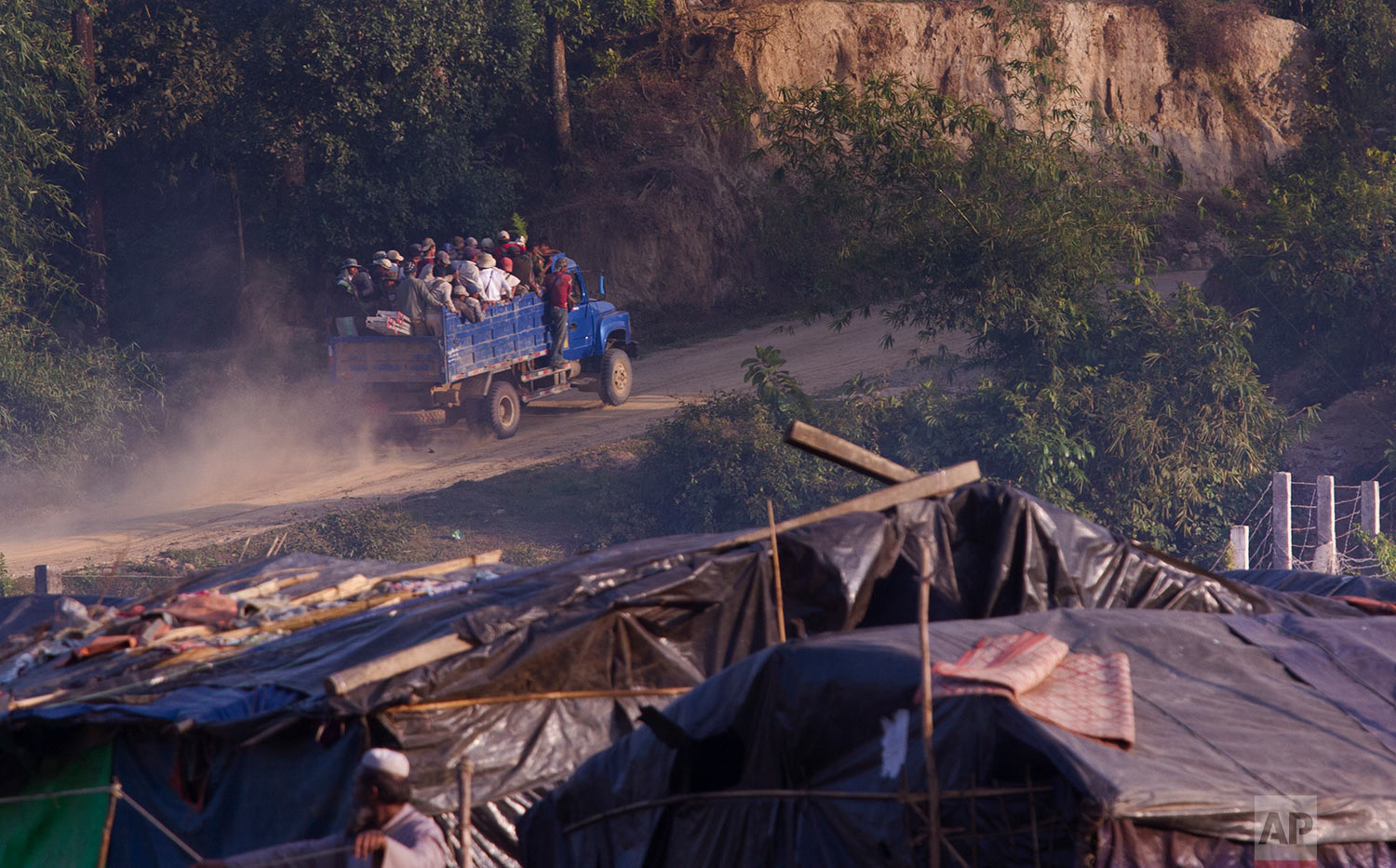 In this Tuesday, Jan. 23, 2018, photo, a Myanmar truck is seen carrying road construction workers huddled in its back, drives past Rohingya make shift shelters on the Bangladesh side at the Myanmar Bangladesh border at Tumru, near Cox's Bazar. Myanmar says it's ready for a gradual repatriation of Muslim Rohingya refugees chased out by the Buddhist-majority country's military. (AP Photo/Manish Swarup)   See these photos on AP Images